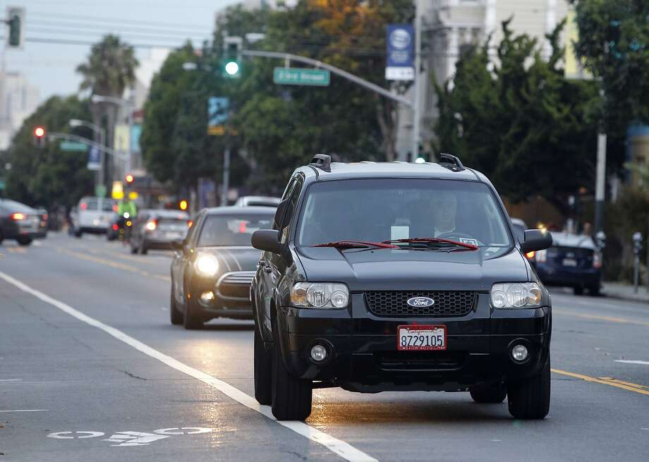 John Sollars drives his SUV on Valencia Street waiting to pick up passengers requesting the UberX ride service in San Francisco, Calif. on Tuesday, Oct. 27, 2015. Sollars generally avoids areas designated by Uber for surge pricing and concentrates more on his own strategy. Photo: Paul Chinn, The Chronicle