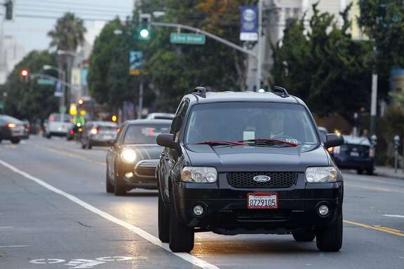 John Sollars drives his SUV on Valencia Street waiting to pick up passengers requesting the UberX ride service in San Francisco, Calif. on Tuesday, Oct. 27, 2015. Sollars generally avoids areas designated by Uber for surge pricing and concentrates more on his own strategy.