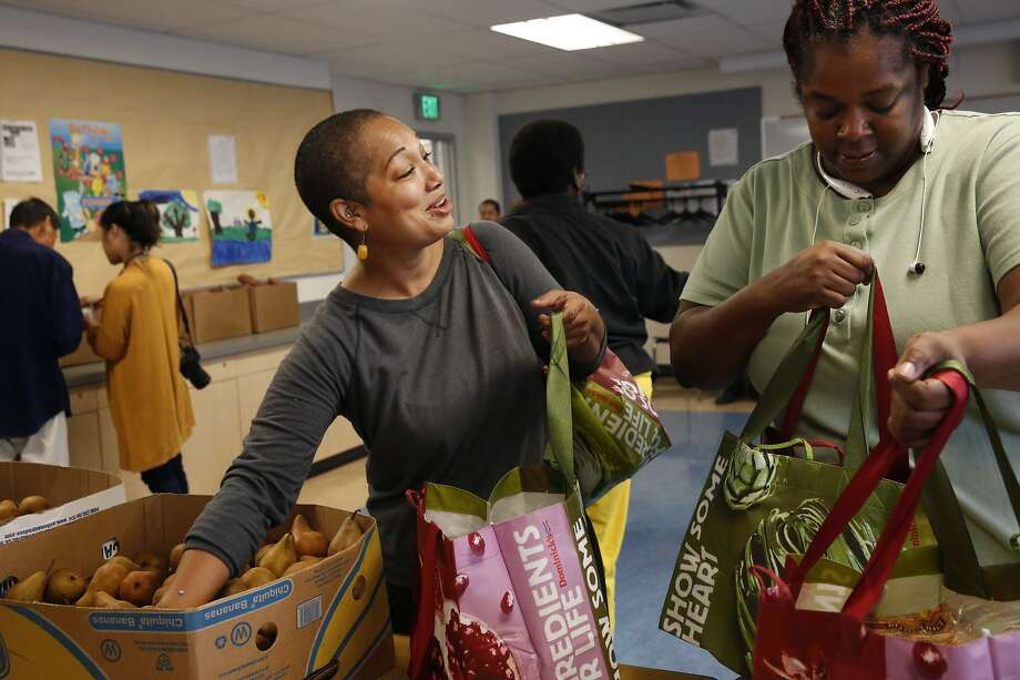 Tara Scott, left, chats with Tamara Shavers as they collect free food at a food pantry put on by Alameda County Community Food Bank at West Oakland Middle School Oct. 27, 2015 in Oakland, Calif. The pantry is open every second and fourth Tuesday from 8-9:30am and 3-4:30pm. Scott, who discovered the pantry only that day, says it's a blessing for her. Scott has been dogged by difficult health issues that make it impossible to work at times. She is also the single mother of two boys and says the food will help her immensely. Photo: Leah Millis, The Chronicle