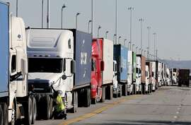 Big rig trucks line up to enter the Port of Oakland terminals on Tuesday January 13, 2015, in Oakland, Calif.