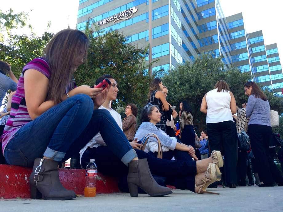 People wait after being evacuated from a high-rise office building at Jones Maltsberger and Loop 410.