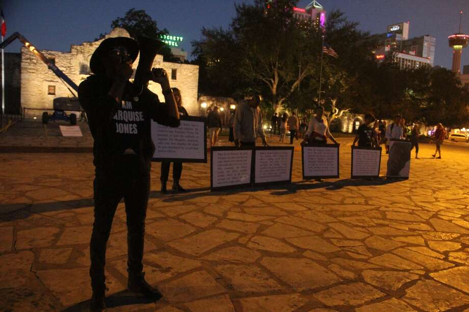 Mike Lowe, organizer with SATX4, speaks statements about the late Marquise Jones as activists hold signs Monday night, Oct. 26, at the Alamo Plaza.