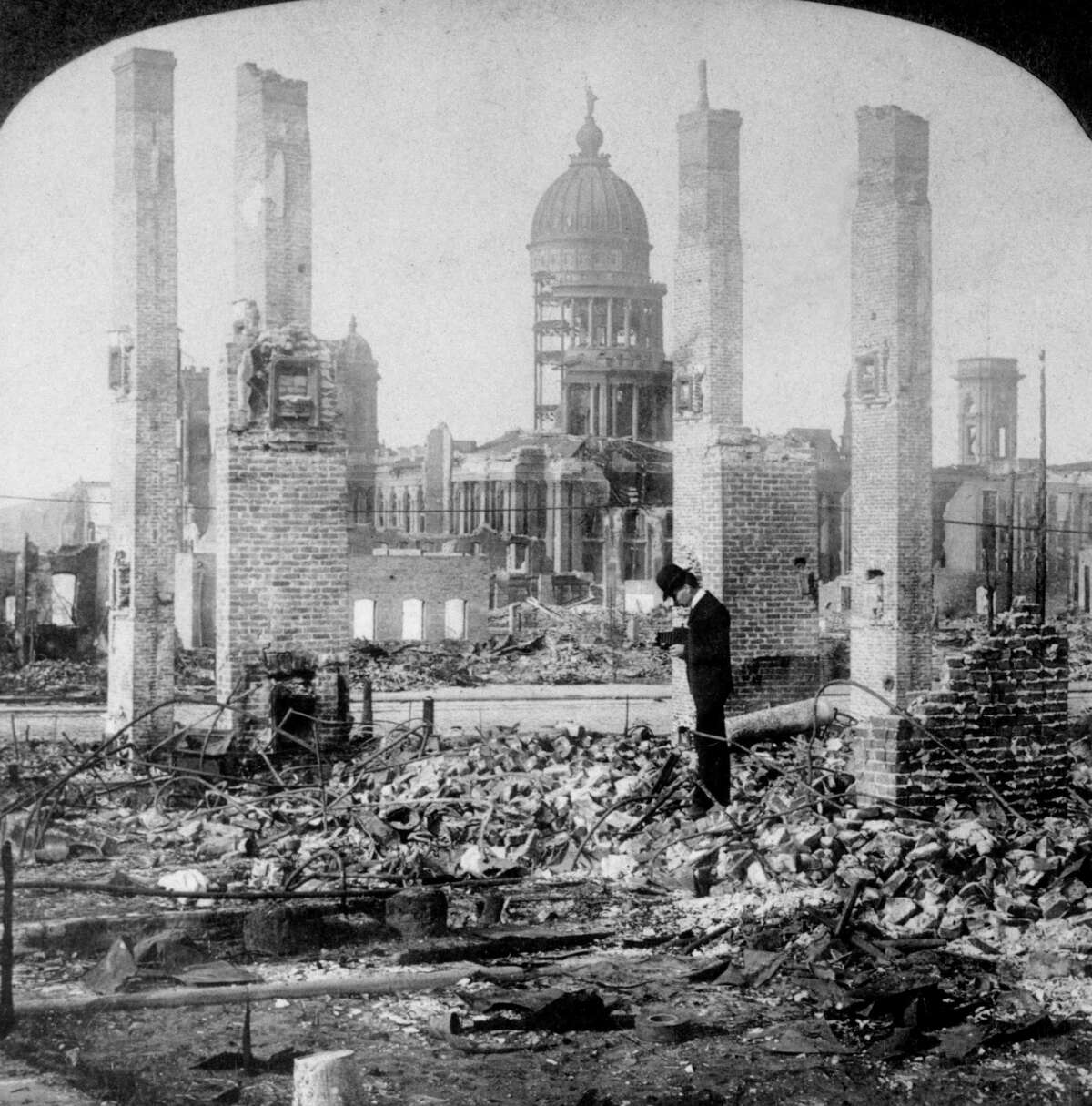 1906: A man photographs the ruins of a building block in front of the remains of City Hall after the earthquake.