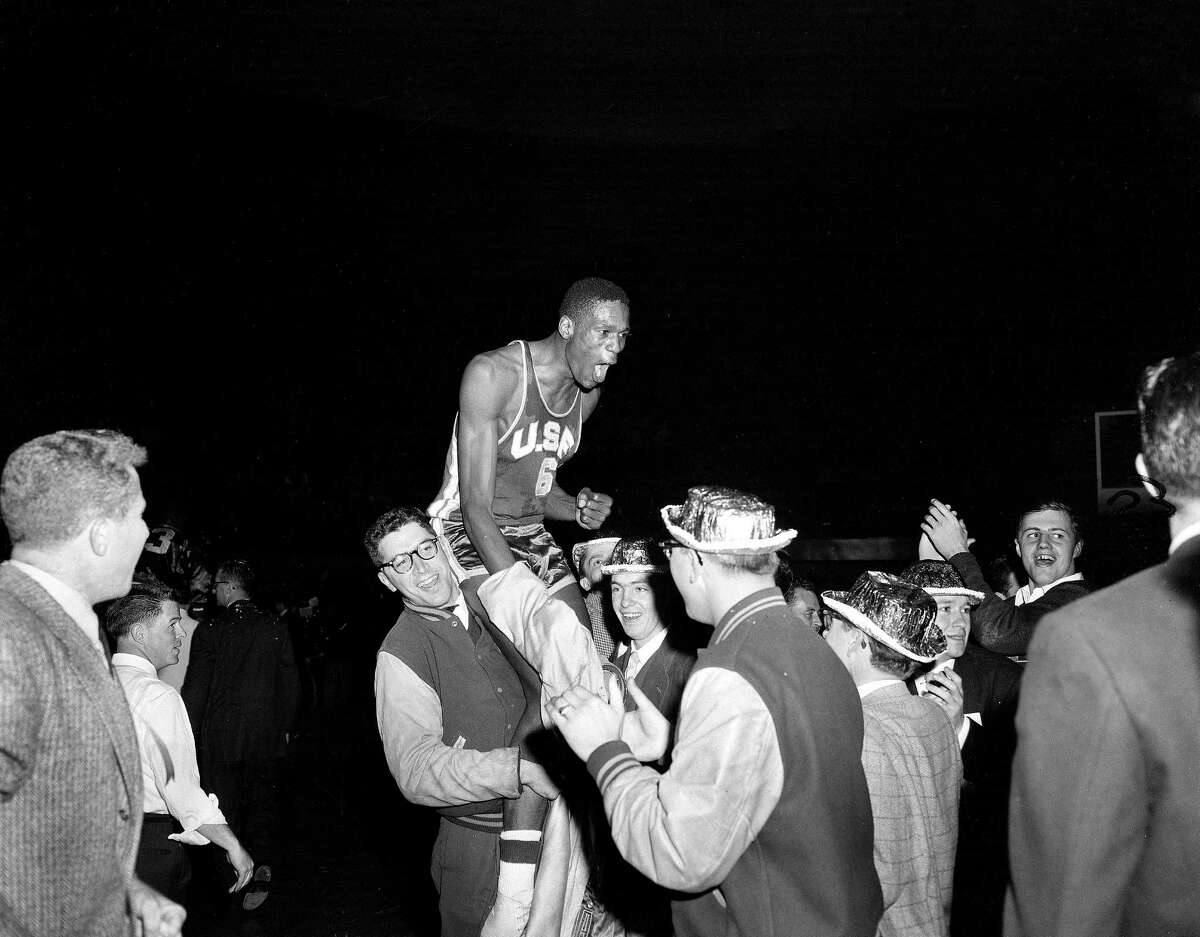 Jubilant USF students carry center Bill Russell off the court after the Dons beat LaSalle at Kansas City's Municipal Auditorium on March 19, 1955, to win their 26th consecutive game and the NCAA basketball championship.