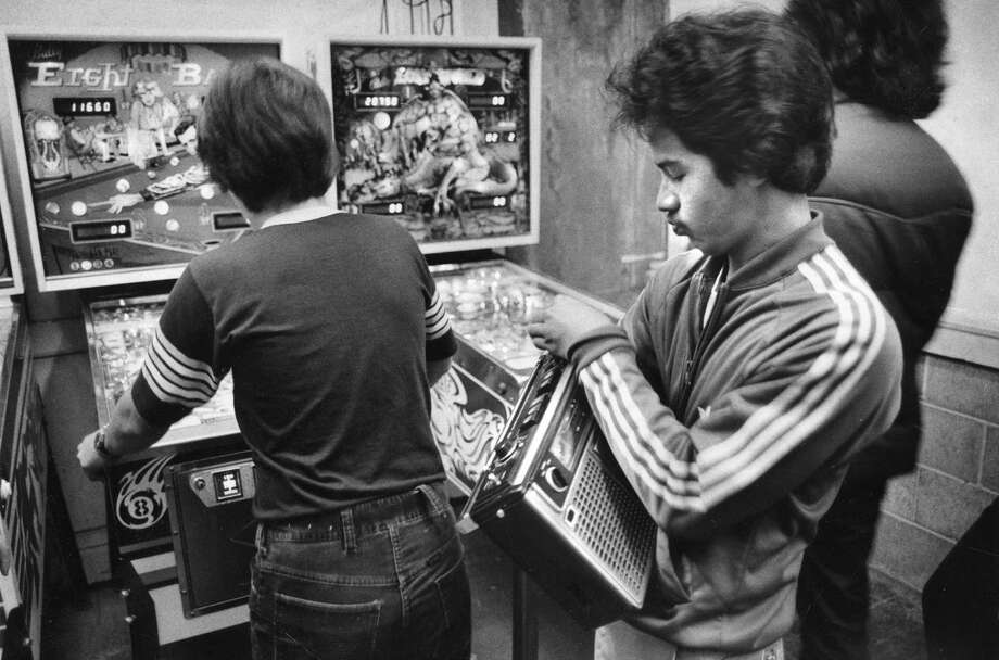 Mark Moreno listens to the radio while his friends play pinball at the Musee Mecanique at the Cliff House in October 1978. Photo: Gary Fong / Gary Fong / The Chronicle 1978 / ONLINE_YES