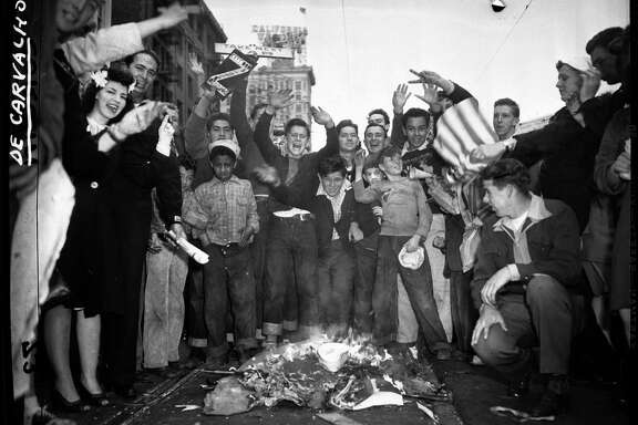 A small crowd of children, young men and adults celebrate the end of World War II on V-J Day with a small fire on Market Street.