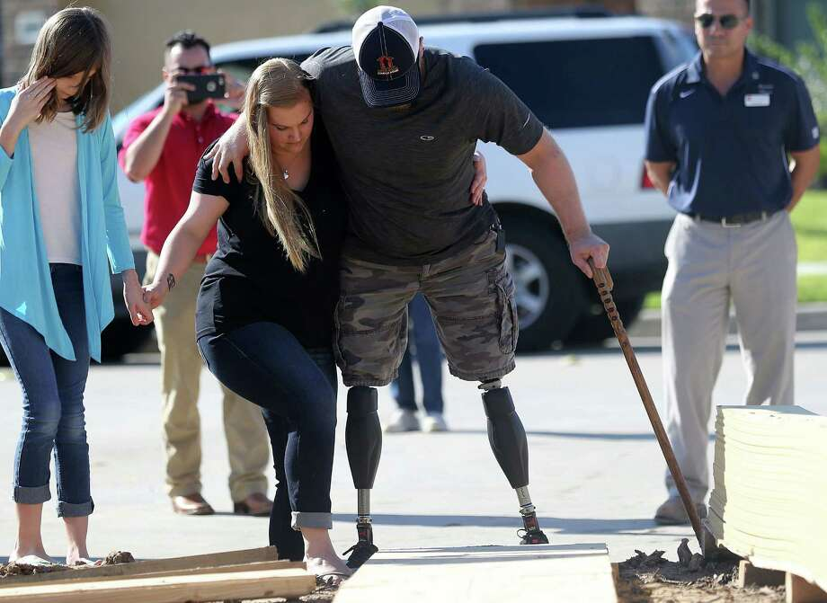 U.S. Marine Corps Cpl. Jonathan Dowdell  gets some assistance from his wife, Rebecca, with their daughter Kitura, 11, as they approach their new house Tuesday, Oct. 27, 2015 in League City, Texas. Photo: Elizabeth Conley / © 2015 Houston Chronicle