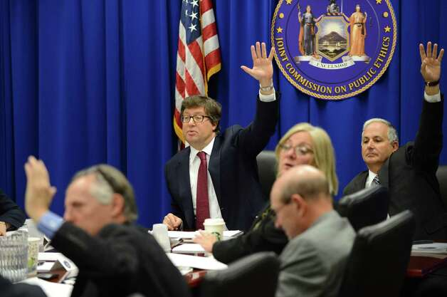Joint Commission on Public Ethics chair, Daniel J. Horowitz, center, and commission members Michael A. Romeo, right, and Seymour Knox, IV, left, raise their hands to vote during a JCOPE meeting Tuesday morning, Oct. 27, 2015, in Albany, N.Y. (Will Waldron/Times Union) Photo: Will Waldron / 00033954A