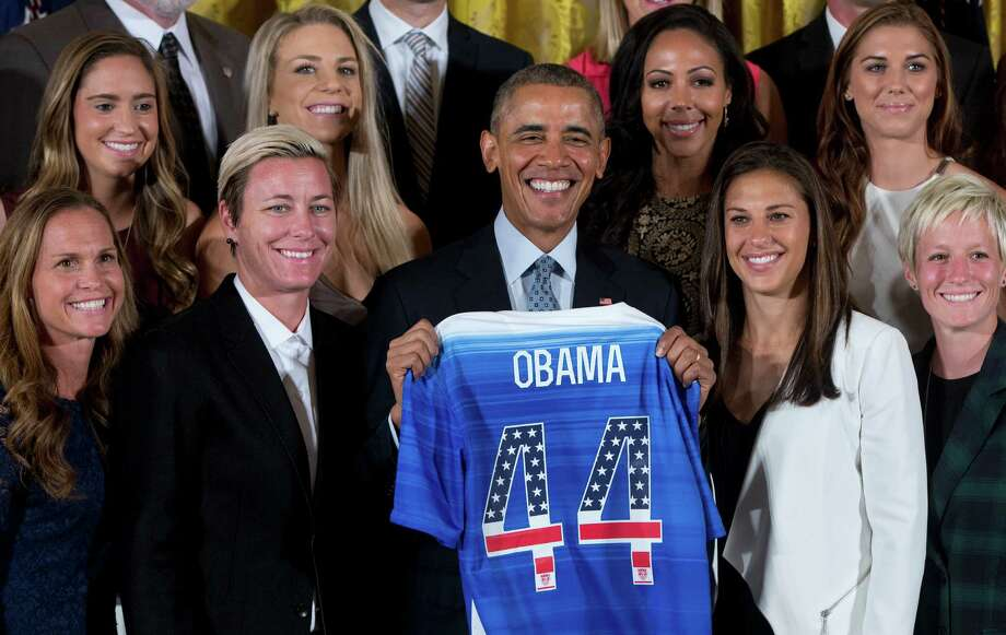 President Barack Obama poses for photos with a jersey he received from head coach Jill Ellis as he welcomed the U.S. Women's National Soccer Team, Tuesday, Oct. 27, 2015, in the East Room of the White House in Washington during a ceremony to honor the team and their victory in the 2015 FIFA Women's World Cup. Standing with Obama, from left are, Christie Rampone, Morgan Brian, Abby Wambach, Julie Johnston, Obama, Sydney Leroux, and Carli Lloyd, Alex Morgan, and Megan Rapinoe.  (AP Photo/Carolyn Kaster) ORG XMIT: DCCK107 Photo: Carolyn Kaster / AP