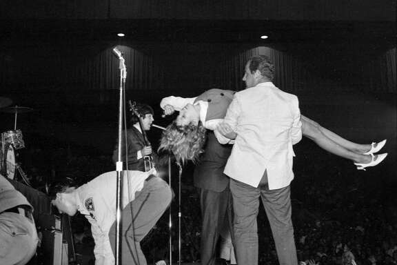 The Beatles are mobbed by fans at the Cow Palace in August 1965.