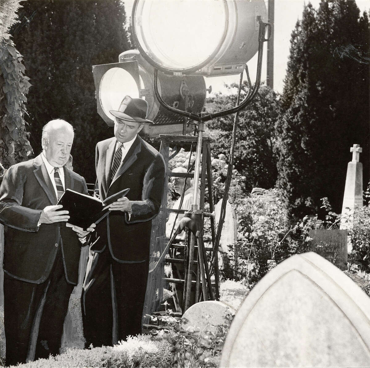 A behind-the-scenes photo shows director Alfred Hitchcock with James Stewart at Mission Dolores during the filming of