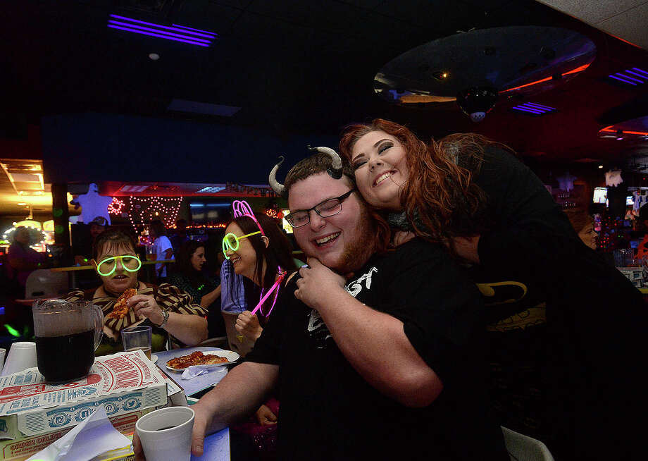 Destiny Deslatte jokes with teammate Will Richards as she gives him a playful hug while they and friends enjoy the Cosmic Costume Bowling Tournament, hosted by the Greater Port Arthur Chamber of Commerce Ambassadors at the Max Bowl Event Center. Teams dressed in themed costumes enjoyed pizza and a silent auction, as well as raffle drawings, and vied for best costume trophies in addition to a win on the lanes. Photo taken Tuesday, October 27, 2015 Kim Brent/The Enterprise Photo: Kim Brent / Beaumont Enterprise