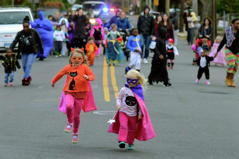 Clementine Beach, 5, and her sister Violet, 2, take part in the Halloween parade along Ellsworth Street in the Black Rock section of Bridgeport on Tuesday. The parade ended at the Black Rock branch of the Bridgeport Public Library, where children could enjoy scary stories, food and goodie bags. Photo: Christian Abraham / Hearst Connecticut Media / Connecticut Post