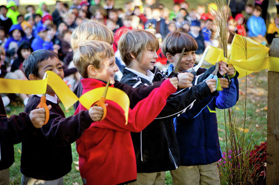 Brunswick School lower-schoolers, left to right, Jonathan Pasteelnick, Thomas Armstrong, Owen Unger, and Thomas Rockman cut the ribbon at the opening ceremony for Brunswick's new schoolyard Habitat and outdoor classroom. Photo: Contributed Photo / (c) 2015 Brunswick School