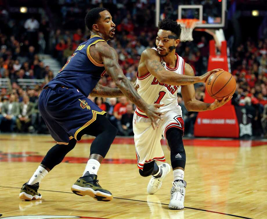 Chicago Bulls guard Derrick Rose (1) makes a pass around Cleveland Cavaliers guard J.R. Smith (5) during the second half of an NBA basketball game Tuesday, Oct. 27, 2015, in Chicago. The Bulls won the game 97-95. (AP Photo/Jeff Haynes) ORG XMIT: CXA122 Photo: Jeff Haynes / FR171008 AP