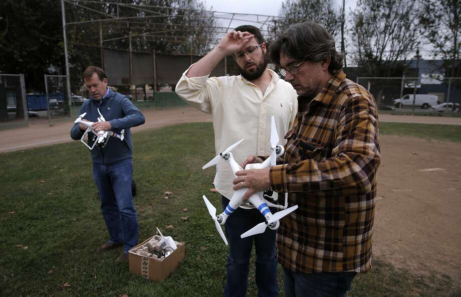 Students Bill Rollinson, (left) and David Golden, (right) get their crafts set up by instructor Brian Burdett, during a drone flying workshop at Jackson Park  in San Francisco, Calif. on Tues. October 27, 2015.The workshop is being put on by the company Lumoid who rents consumer electronic gadgets including drones. Photo: Michael Macor, The Chronicle