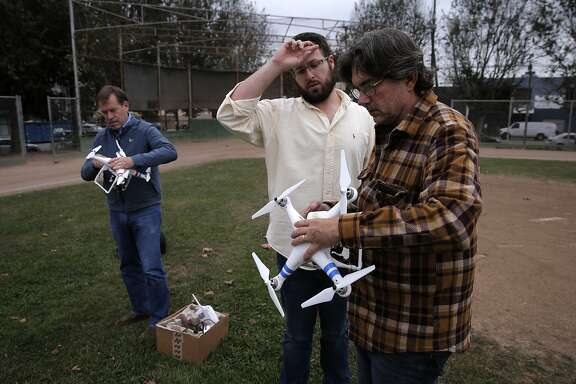 Students Bill Rollinson, (left) and David Golden, (right) get their crafts set up by instructor Brian Burdett, during a drone flying workshop at Jackson Park  in San Francisco, Calif. on Tues. October 27, 2015.The workshop is being put on by the company Lumoid who rents consumer electronic gadgets including drones.