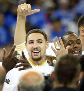 Golden State Warriors' Klay Thompson and Harrison Barnes show off their NBA Championship ring after ceremony before playing New Orleans Pelicans during NBA game at Oracle Arena in Oakland, Calif., on Tuesday, October 27, 2015.