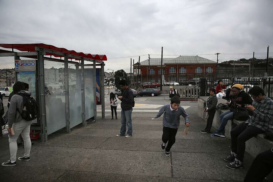 About a hundred units of affordable housing might replace the parking lot on the southwest corner of San Jose and Geneva avenues (behind pedestrians) in San Francisco, Calif., on Tuesday, October 27, 2015. Photo: Liz Hafalia, The Chronicle