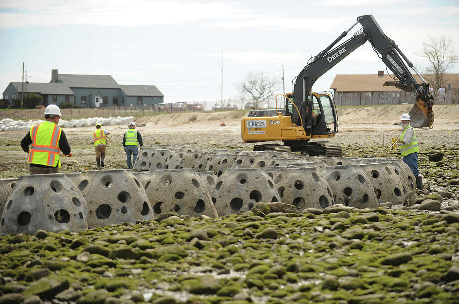 """Concrete Reef Balls are guided into place during the installation of a """"living shoreline"""" on the Audubon property on Stratford Point in Stratford, Conn. on Tuesday, May 6, 2014. Submerged at high tide, the barrier reduces storm erosion by dissipating the power of waves while at the same time provides living environments for tide zone fauna. Photo: Brian A. Pounds / Brian A. Pounds / Connecticut Post"""