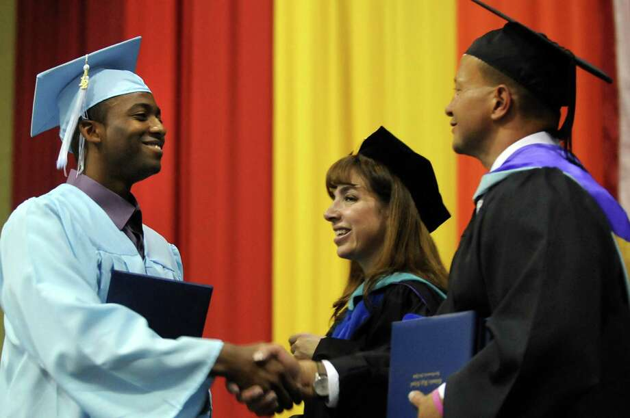 Graduate Vanier Francis, left, receives his diploma from superintendent Angela Nagle, center, and principal John Sawchuk during the Columbia High commencement exercises on Saturday, June 23, 2012, at the Hudson Valley Community College in Troy, N.Y. (Cindy Schultz / Times Union) Photo: Cindy Schultz, Albany Times Union / 00018129A