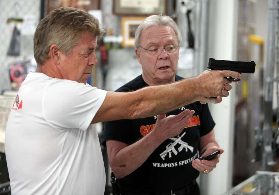 Dave Odlin listens to Jim Pruett, owner of Jim Pruett's Gun's & Ammo store, about gun features on Wednesday, Oct. 2, 2013, in Houston. Odlin purchased a Springfield semi-automatic handgun which arrived to the store today, and sold 10 minutes after it was placed in the display case.  Gun stores need to provide the federal form to customers to fill out in order to receive permission to purchase the weapon. Texas has more than 1 million people who have filled out form.  ( Mayra Beltran / Houston Chronicle ) Photo: Mayra Beltran, Houston Chronicle