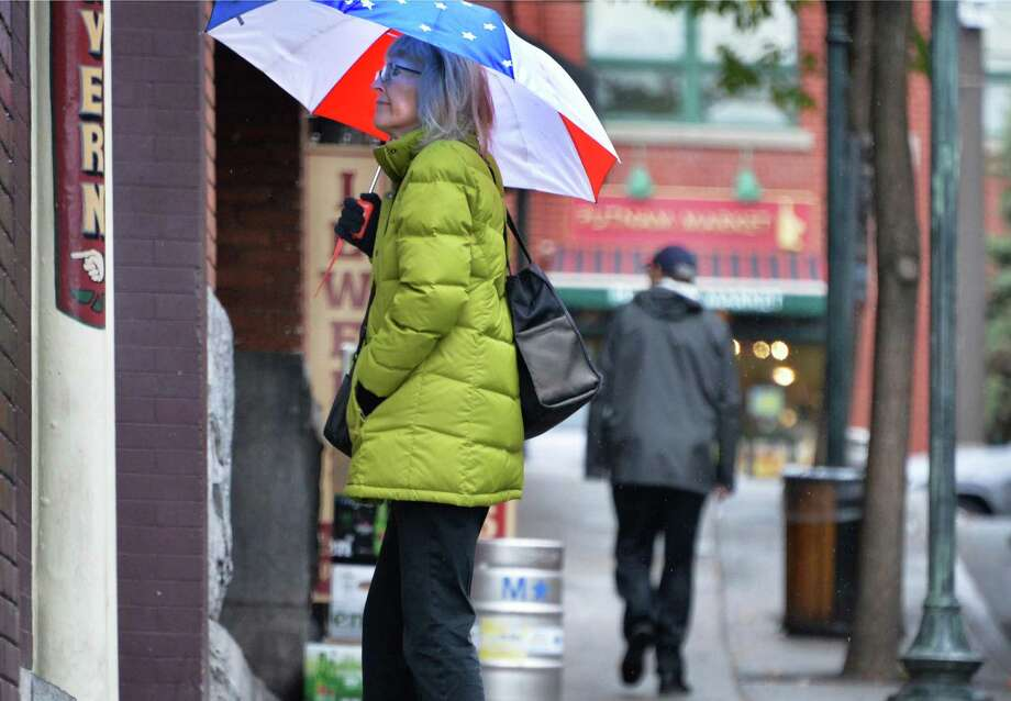 Zoe Nousiainen of Saratoga Springs stops to window shop during a rainy walk home Wednesday Oct. 28, 29015 in Saratoga Springs, NY.  (John Carl D'Annibale / Times Union) Photo: John Carl D'Annibale