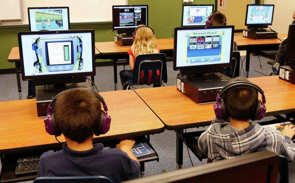 FILE - In this July 21, 2014 file photo, students at a summer reading academy at Buchanan elementary school work in the computer lab at the school in Oklahoma City. (AP Photo/Sue Ogrocki,File) ORG XMIT: WX106