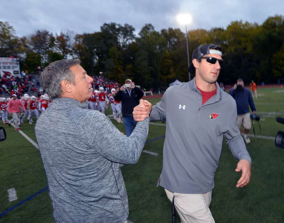 At right, Greenwich High School head football coach John Marinelli, shakes hands with his father, Lou Marinelli, just after losing to his father's New Canaan High School football team by a score of 24-14 at Greenwich, Conn., Saturday, Oct. 24, 2015. Lou Marinelli is the head coach of the New Canaan High School football team. Photo: Bob Luckey Jr., Hearst Connecticut Media