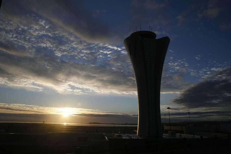 The sun rises behind the new air traffic control tower at SFO in San Francisco, Calif. on Wednesday, Oct. 28, 2015. The state-of-the-art 231-foot tower will replace the older and shorter version when it becomes fully operational in July 2016. Photo: Paul Chinn, The Chronicle