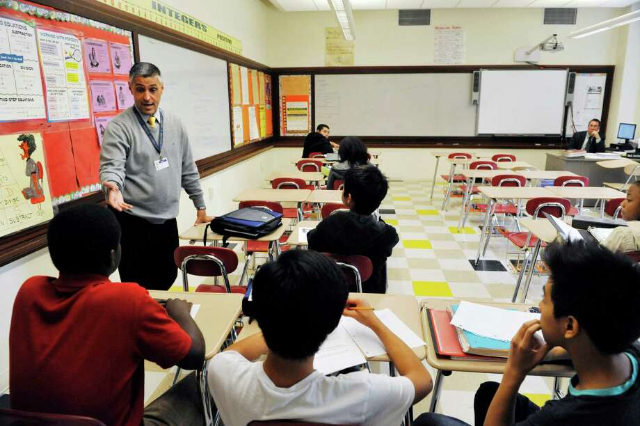 Hackett Middle School principal, Michael Paolino, talks with students in an enrichment eighth grade class during a community tour at the school on Wednesday, October 28,  2015 in Albany, N.Y.  The enrichment periods during the school day allow students to work on community service learning based projects.   Albany officials, community leaders, and parents held an event at the school on Wednesday to show their support for the school and announce a renewed commitment to its success.  The school has been identified by New York State as persistently struggling.  (Paul Buckowski / Times Union) Photo: PAUL BUCKOWSKI / 00033972A