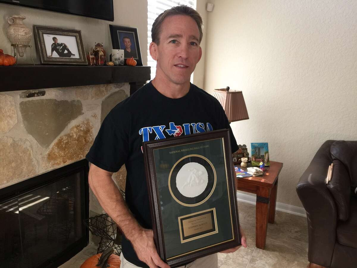 Retired Air Force senior master sergeant Steve Horton of Cibolo shows a copy of the plaque honoring him that now hangs in the National Wrestling Hall of Fame in Stillwater, Okla. The St. Louis native's new mission is to make Texas a competitive wrestling state.