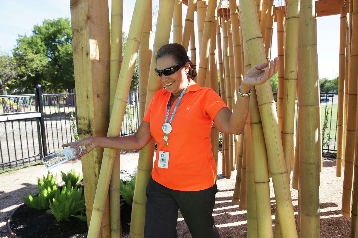 Maria Vasquez emerges from a noisy pass through a bamboo curtain designed to stimulate senses as she and others tour the facilities during the grand opening of the Harvey Najim Hope Center at the Children's Shelter on Oct. 28.