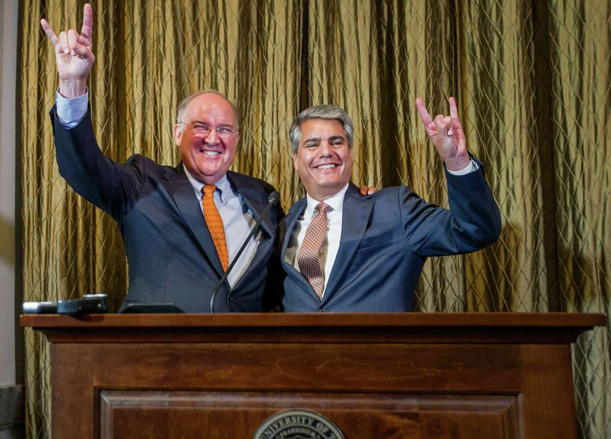"""Texas athletic director Michael Perrin, left, and UT president Greg Fenves give the """"Hook 'em Horns"""" sign during a news conference on Sept. 16, 2015, in Austin, Texas."""