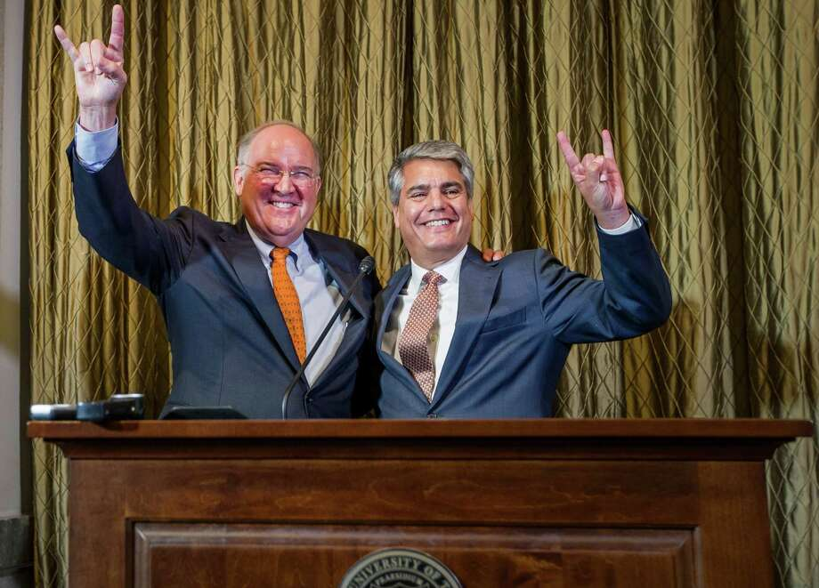 "Texas athletic director Michael Perrin, left, and UT president Greg Fenves give the ""Hook 'em Horns"" sign during a news conference on Sept. 16, 2015, in Austin, Texas. Photo: Ricardo B. Brazziell /Austin American-Statesman / Austin American-Statesman"