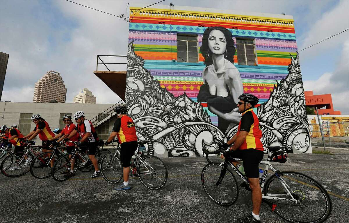 Ralph Ximenes (right) and other members of the cycling group, Street Ratz, stop at a mural near North St. Mary's and Richmond avenues before embarking on a ride around the city July 11.