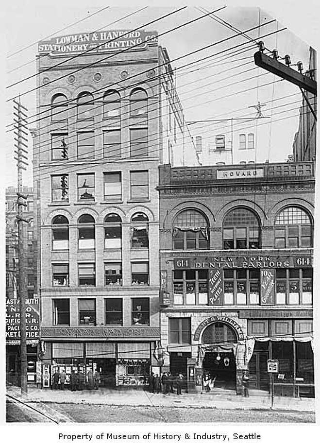 """""""In 1882, James Lowman and Clarence Hanford joined forces to found Lowman & Hanford Stationery and Printing Company. After losing their original building in the Great Fire of 1889, the partners reopened the business at 616 First Avenue. There, they expanded into publishing, bookbinding and book selling, and even sold photographic equipment and other supplies to people leaving for the gold fields. In 1902-3, the firm built a large new building next door, on the corner of First Avenue and Cherry Street."""" -MOHAI. This photo shows the building in roughly 1899. Photo courtesy MOHAI, Anders B. Wilse Collection, image number 1988.33.73. Photo: Courtesy MOHAI"""
