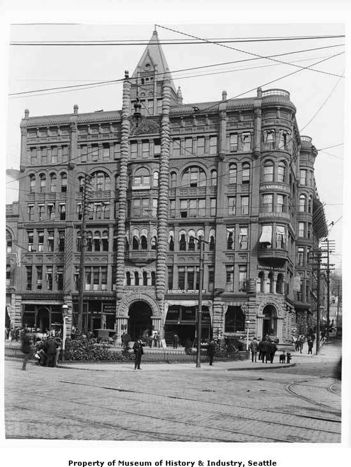 """Finished in 1892 and standing 110 feet tall, the Pioneer Building was Seattle's tallest building for 12 years. """"Many of the wooden buildings destroyed in Seattle's 1889 fire were replaced with large, modern brick buildings. Businessman Henry Yesler commissioned the Pioneer Building on the site of his original Seattle home. At the time this photo was taken, the building housed insurance agents, a bank, law offices, a cigar store, and an agency which sold tickets to Alaska.The brick and stone building still stands at Pioneer Square. This photo, taken between 1897 and 1900, shows the Pioneer Building at the corner of First Avenue and James Street in Pioneer Square. Awnings shade some of the windows on the ground and upper floors. Earthquakes later weakened the tall tower above the front entrance, and the tower was removed sometime in the 1930s."""" -MOHAI. Photo courtesy MOHAI, Anders B. Wilse Collection, image number 1988.33.49."""