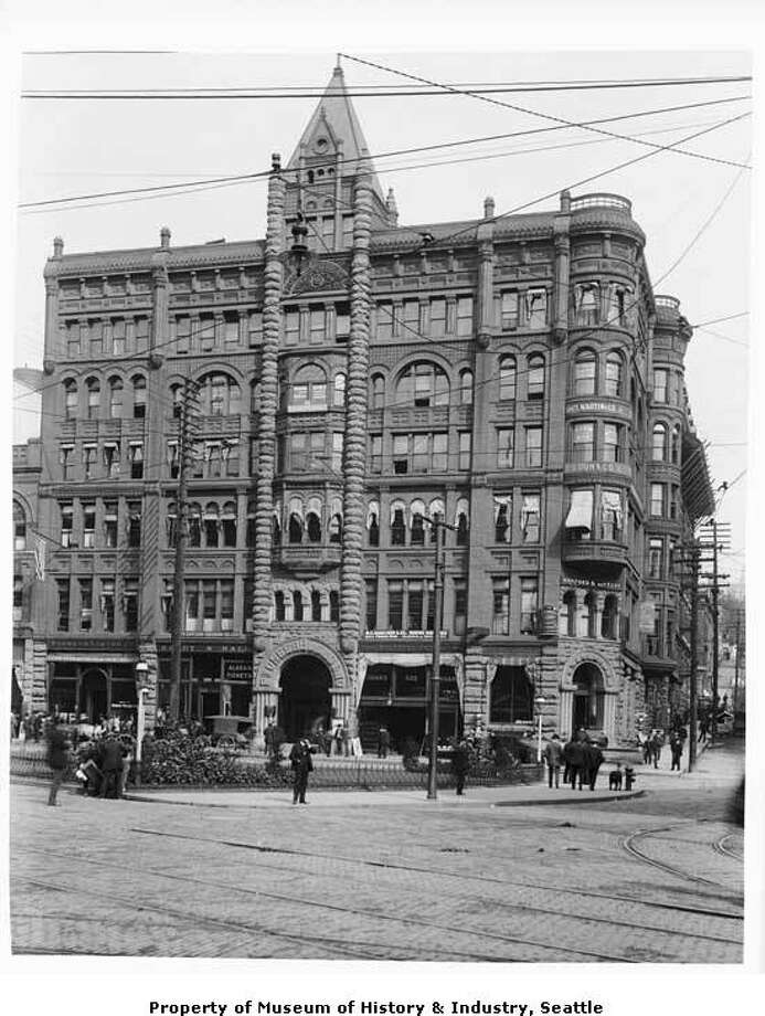 """Finished in 1892 and standing 110 feet tall, the Pioneer Building was Seattle's tallest building for 12 years. """"Many of the wooden buildings destroyed in Seattle's 1889 fire were replaced with large, modern brick buildings. Businessman Henry Yesler commissioned the Pioneer Building on the site of his original Seattle home. At the time this photo was taken, the building housed insurance agents, a bank, law offices, a cigar store, and an agency which sold tickets to Alaska. The brick and stone building still stands at Pioneer Square. This photo, taken between 1897 and 1900, shows the Pioneer Building at the corner of First Avenue and James Street in Pioneer Square. Awnings shade some of the windows on the ground and upper floors. Earthquakes later weakened the tall tower above the front entrance, and the tower was removed sometime in the 1930s."""" -MOHAI. Photo courtesy MOHAI, Anders B. Wilse Collection, image number 1988.33.49. Photo: Courtesy MOHAI"""