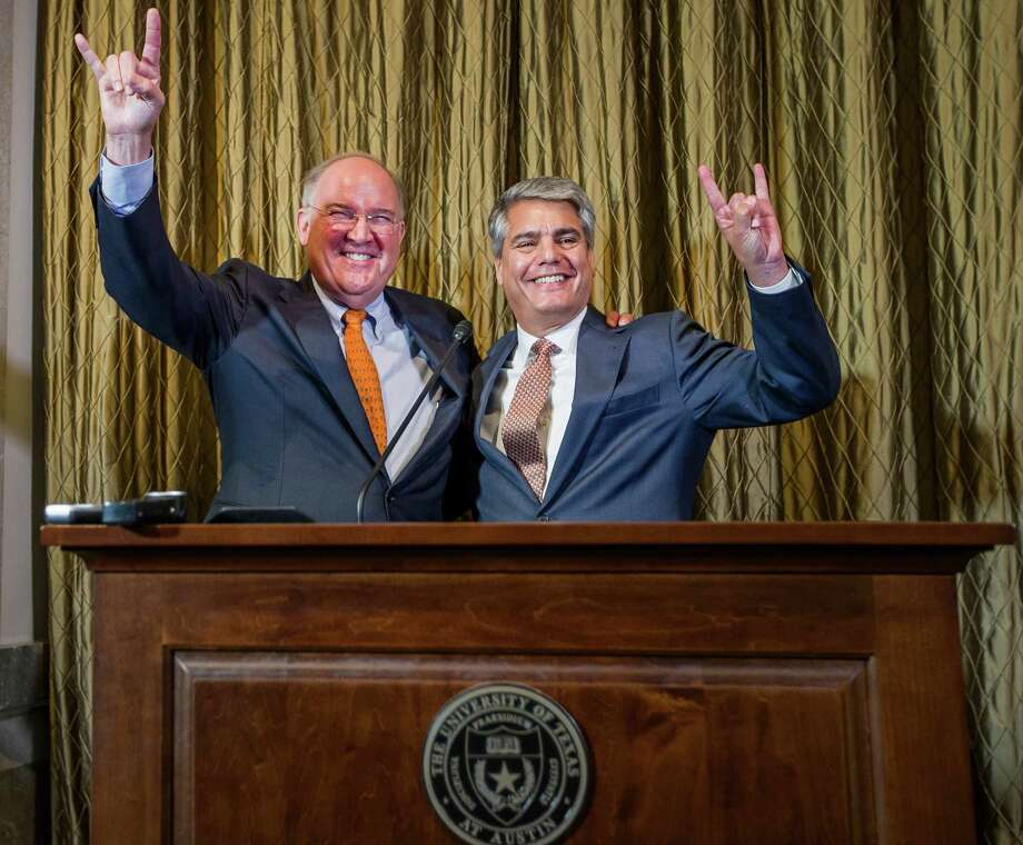 """Interim Texas athletic director Michael Perrin, left, and University of Texas President Greg Fenves give the """"Hook 'em Horns"""" sign during a news conference, Wednesday, Sept. 16, 2015, in Austin, Texas. Perrin is a former Texas linebacker. (Ricardo B. Brazziell/Austin American-Statesman via AP) Photo: RICARDO B. BRAZZIELL, MBO / Austin American-Statesman"""