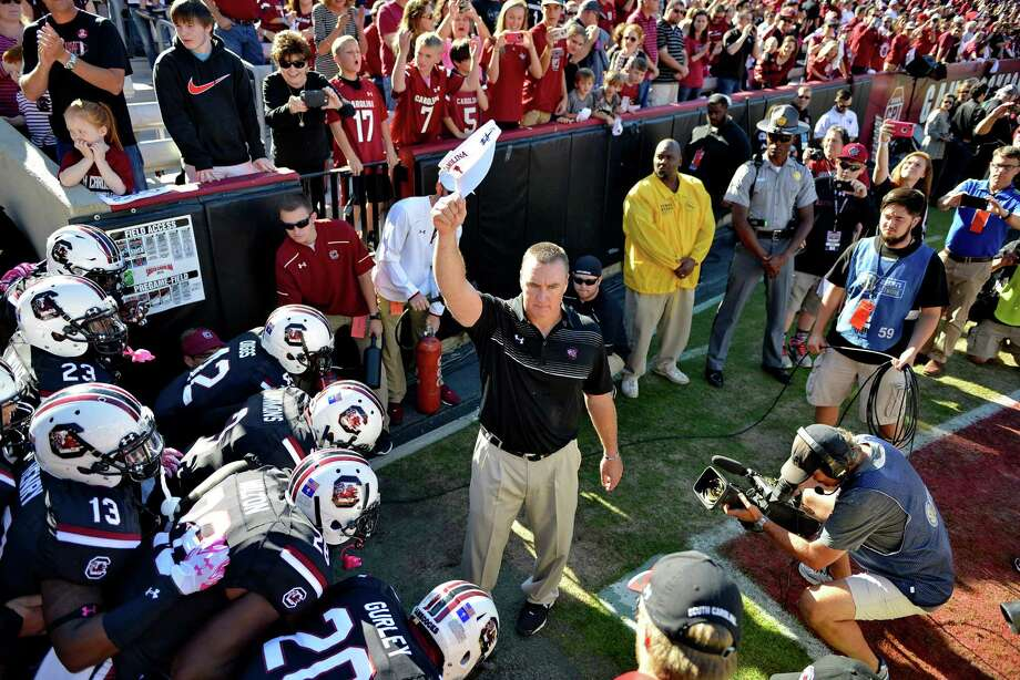 South Carolina interim head coach Shawn Elliott, center, holds up a visor in honor of ex-head coach Steve Spurrier before an NCAA college football game against Vanderbilt, Saturday, Oct. 17, 2015, in Columbia, S.C. (AP Photo/Richard Shiro) Photo: Richard Shiro, FRE / FR159523 AP