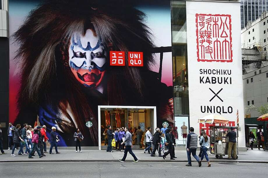 Shoppers walk past the entrance to the UNIQLO store on Fifth Avenue in Midtown Manhattan in New York City on April 26, 2015. The Japanese casual wear designer, manufacturer and retailer has collaborated with the kabuki company Shochiku to produce a line of clothing inspired by traditional kabuki motifs. (Photo by Robert Alexander/Getty Images) / 2015 Robert Alexander