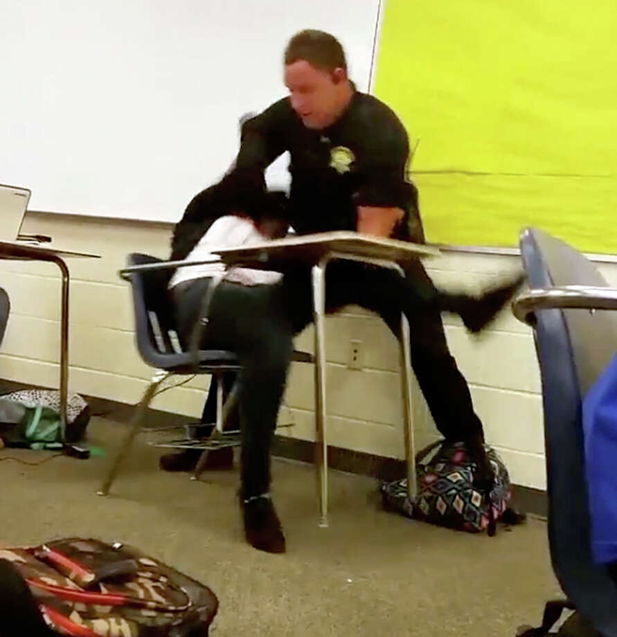 In this Oct. 26 photo made from video taken by a Spring Valley High School student, Senior Deputy Ben Fields tries to forcibly remove a student who refused to leave her high school math class in Columbia, S.C. Photo: HONS / Student