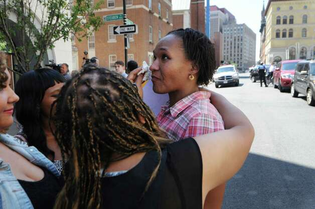 "Aisha Dixon, the mother of Marquis Dixon, right, is comforted by family members during a press conference and rally outside Albany District Attorney David Soares' office Monday, Aug. 10, 2015, in Albany, N.Y. Advocates called on the district attorney to publicly call the nine-year sentence teen Marquis Dixon received for stealing sneakers excessive and to support Raise the Age legislation that has awaits action by the state Legislature next year. They also called on him to finish an investigation into the police-related death of Donald ""Dontay"" Ivy, deliver indictments against the three officers involved and publicly support the use of a special prosecutor in cases of police killings of civilians. (Will Waldron/Times Union) Photo: WILL WALDRON / 00032956A"