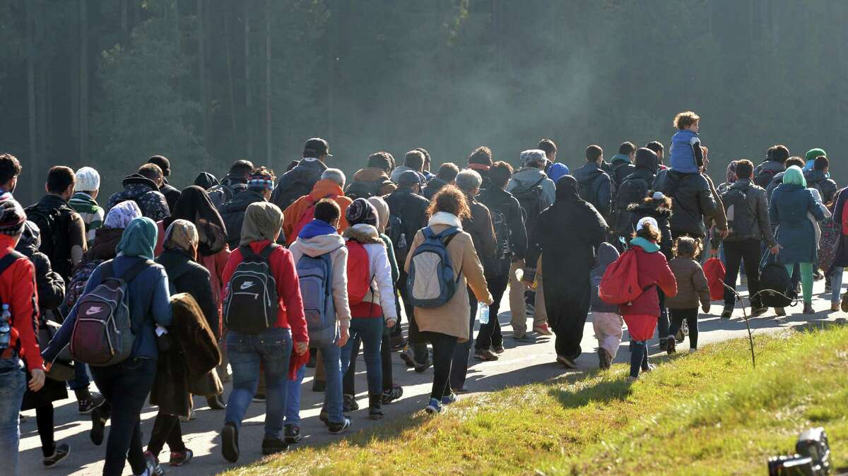 Migrants continue their trek Wednesday after crossing the border between Austria and Germany in Wegscheid near Passau. Germany has implemented a plan to streamline the asylum process for those fleeing civil war, such as Syrians, to settle them more quickly.