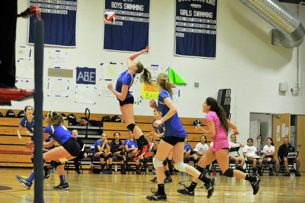 Darien varsity volleyball player Izzy Taylor, center, jumps sky high to slam a ball over the net during a match against Greenwich at Darien High School on Wednesday, Oct. 28, 2015.
