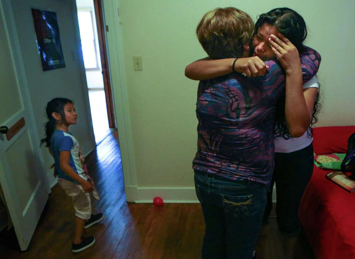 Mirian Escobar Perez, 23, far right, of Honduras cries and is comforted by Rosie at the Mennonite Casa de Maria y Marta shelter on Monday, April 2, 2015. The Mennonite Casa de Maria y Marta is where immigrant women and their children stay after being released from detention centers in South Texas and participates as part of the Interfaith Welcome Coalition.