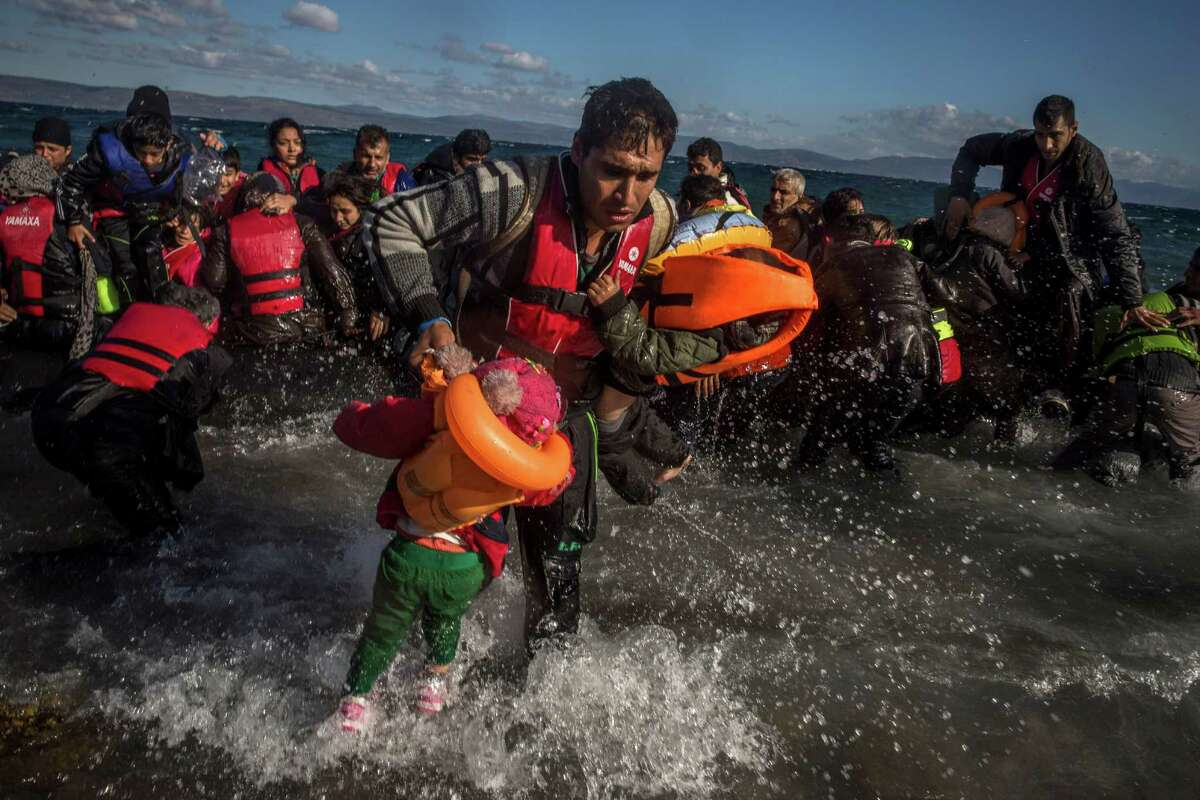 Afghan migrants disembark from their frail boat on the Greek island of Lesbos after crossing the Aegean Sea from Turkey.