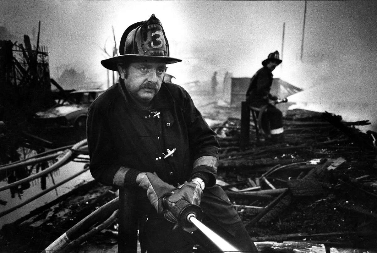 July 14, 1981: A firefighter leans against a pole, while dousing embers at the end of fighting a blaze in San Francisco.
