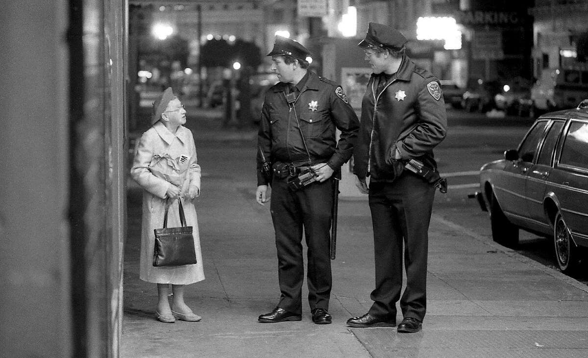 San Francisco Police Department officers patrol The Tenderloin. These officer walk a resident to her home April 26, 1985.
